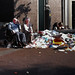 Elderly people and a pile of trash