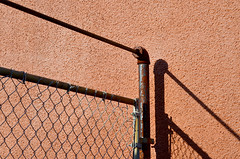 Angle of incidence (James_D_Images) Tags: frontlit red brown rust wall fence pipe weathered stucco chainlink shadows lines angle abstract alley