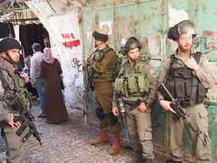 Here Israeli soldiers are watching The settlers as they do a trip thru The old city of Hebron.
