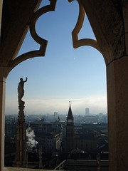 Through a Window (Demy Rub) Tags: window rooftops skyline sky blue tower fume italy upabove travel trip statue city center cloud view