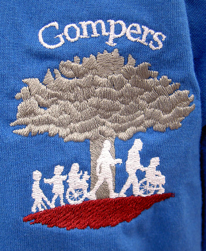 T-shirt with GOMPERS showing a tree and several children and an adult walking.  Some of the children are using crutches or wheelchairs.