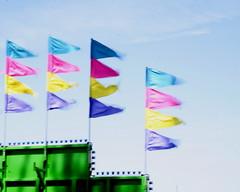 Festive Flags (Living Juicy) Tags: longexposure carnival pink blue green colors yellow purple flags fourthofjuly rides july4th citybeach oakharborwashington