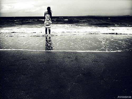 Denize doğru yürüyen hüzünlü bir kadın görseli