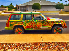 One Love. One Jeep (oybay©) Tags: jeep jeepcherokee cherokee color colors colorful reggae rasta suncitywestarizona suncitywest arizona lowkey subtle beardsleydrive car automobile suv hubcap wheelcover yellow orange blue red green primarycolors cool unique unusual different parked