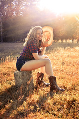Sunshine (Floris M. Oosterveld) Tags: girl cowgirl country straw hat hot shorts hotpants cowboy boots grass warm temperature smile woman sexy attractive flare pose model shorties plaid shirt sunny hair yellow orange face rays sun beautiful western