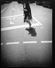 Woman Crossing Street (Mental Octopus) Tags: street blackandwhite bw woman film monochrome photography citylife streetphotography streetscene plasticfantastic scan plastic analogue vignette ilford cityscene debonair plasticlens xp2super400 analoguephotography unrecognizableperson plasticfilmtastic epsonv850 epsonv850pro