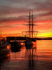 Sunset in Oslo harbour (CecilieSonstebyPhotography) Tags: oslo boat boats harbour iphone orange outdoor red reflections sea ship ships sunset water windows winter yellow norway
