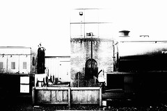 Confrontation and grit (newshot.) Tags: nikon d700 zeiss planart1450 zf2 srps boness steam locomotive railway shed atmosphere grit grime buffers highcontrast blacks whites graphic compositionalplacement dark window watertank dirt brickwork clutter eyesore vignette surfaces textures layers planes orthogonality materials