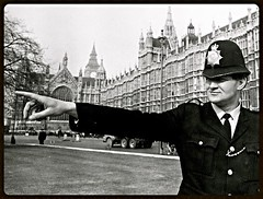 Early 1970's, College Green, Old Palace Yard, Westminster, London, SW1. UK. Metropolitan Police Constable 635 'A' John Holley Gives Directions To A Tourist. Palace of Westminster (Houses of Parliament) & 'Big Ben' In Rear. (sgterniebilko) Tags: uk houses london westminster station square traffic ad police parliament delta palace row points cannon division alpha metropolitan whitehall constables a