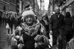 Furry Christmas (Leanne Boulton) Tags: people monochrome depthoffield urban street candid portrait portraiture streetphotography candidstreetphotography candidportrait eyecontact candideyecontact streetlife woman female face facial expression eyes look emotion feeling fur furry winter clothing fashion style christmas hat fun tone texture detail bokeh natural outdoor light shade shadow city scene human life living humanity society culture canon 5d canon5dmkiii 70mm character ef2470mmf28liiusm black white blackwhite bw mono blackandwhite glasgow scotland uk