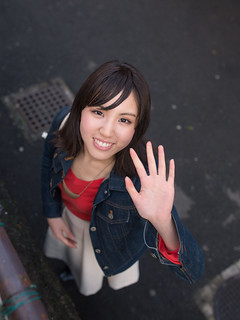 Young woman looking up and waving hands on street