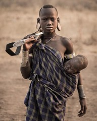 Mursi Tribe Girl with a baby and a rifle, Omo Valley, Ethiopia. (C) Joel Santos - www.joelsantos.net (Joel Santos - Photography) Tags: instagram mursi tribe girl with baby rifle omo valley ethiopia c joel santos wwwjoelsantosnet