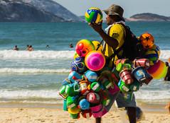 Colorido ambulante (mcs.moisesfilho) Tags: brasil brazil praia ambulantes vendedores cores água óculos mar ocean sand areia rio de janeiro rj onda wave beach blue azul bolas brinquedos