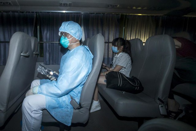 A health worker with protective suits sitting with people (R) who came into close contact with the Korean Mers patient arrive at Lady MacLehose Holiday Village in Sai Kung, where they will spend two weeks in quarantine, in Hong Kong, China
