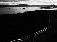 Holy Island in the Evening (cycle.nut66) Tags: sea sky blackandwhite art film monochrome silhouette clouds contrast fence boats four bay high harbour olympus hills filter micro mooring grainy grayscale mainland thirds evolt epl1 mzuiko
