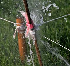 soft explosion (~nevikk~) Tags: red brown white green water lawn waterdroplets waterstream lawnsprinkler splashingwater markingpole markingstring