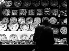 nocturnal market 04 (byronv2) Tags: edinburgh edinburghbynight edimbourg scotland blackandwhite blackwhite bw monochrome peoplewatching candid street night nuit nacht princesstreet princesstreetgardens market streetmarket festivemarket crockery plate plates china stall kiosk