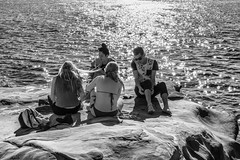 Picnic on the Rock Above the Shining Sea (Pauls-Pictures) Tags: ocean street camera city girls friends sea people urban blackandwhite beach boys monochrome lens photography shiny rocks picnic fuji candid australia cliffs bikini fujifilm standard shining sparkling streetphotos compactcamera terrigal streetpics streetphotograhy achromatic xt1 streetpictures fxlens mirrorlesscamera 35nmf14lens