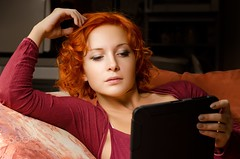 Reading her ebook (pavoljezik) Tags: female tablet computer woman reading technology adult beautiful young home modern one person 20s casual device electronic internet laptop pad touch leisure sofa red book ebook hand indoors pc people digital relaxed looking web portrait alone enjoying hair handheld caucasian life sitting curly