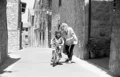 Learnig to ride the bike... (Augusto Gasbarri) Tags: nikon nikonfe2 fe2 filmphotography film fp4 ilford ilfordfp4 rodinal homedeveloped buyfilmnotmegapixels filmisnotdead bike riccardo nipote grandson nonna grandmother