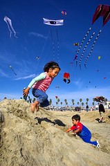 Playing in the sand under the kites (fd) Tags: california family kite beach childhood festival sand shiny daughter son 1870mmf3545g huntingtonbeach themecompetition lightproofboxcom tccomp076