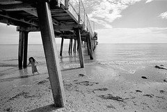 Ghost Child (inaudible) Tags: leica wood sea bw playing beach girl pier lenstagged sand jetty australia adelaide yellowfilter henleybeach voigtlnder21f4colorskopar cv21