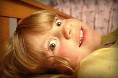 Wide Eyes, Wide Lens (Glenn Loos-Austin) Tags: girl smile rose canon bed eyes child potd bedtime 1022mm 30d testshot photooftheday canon1022mm 22mm canon30d tooyellow thebestyellow