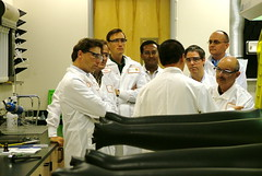 seven men in white lab coats conferring together in a non-specific laboratory