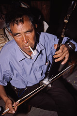 father palying er-hu instrument at family ceremony (AsianInsights) Tags: china travel asia eiffeltower erhu fertilizer tonghai romanachapman gettyimagessoutheastasiaq1