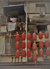 lanterns at a temple (SM Tham) Tags: asia southeastasia malaysia penang georgetown unescoworldheritagesite lebuhchulia chuliastreet hanjiangteochewancestraltemple chinese temple chinesenewyear lanterns building flats apartments facade balconies windows laundry clothes airconditioningunit piping plants fencing wall awning outdoors