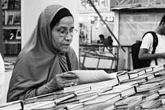 The Bookworm (ainulislam) Tags: book read old woman reading books bookfair february bnw blackandwhite black white muslim bookworm nerd look looking fair bookfest pov dof perspective
