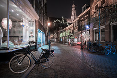 Riding home for Christmas (McQuaide Photography) Tags: haarlem noordholland northholland netherlands nederland holland dutch europe sony a7rii ilce7rm2 alpha mirrorless 1635mm sonyzeiss zeiss variotessar fullframe mcquaidephotography lightroom adobe photoshop tripod manfrotto light licht night nacht nightphotography stad city urban lowlight architecture outdoor outside illuminated street straat warmoesstraat window wideangle wideanglelens groothoek building longexposure oldstreet old oud character traditional authentic streetlight bike bicycle fiets shop winkel shopwindow atmosphere sfeer christmas kerst stbavo grotekerk winter emptystreet deserted nopeople cobblestone cobbles