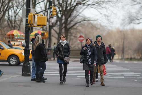 People crossing Central Park South at 7th Avenue.