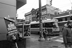 Over There (Georgie_grrl) Tags: pentaxk1000 rikenon12828mm toronto ontario blackandwhite monochrome jchstreetpan400 queenstreetwest kingtextiles overthere sign arrow streetcar ttc bicycle cyclist pedestrian intersection