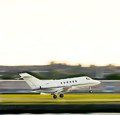 Corporate jet  touching down (Greg Bajor) Tags: city uk travel sky motion blur green london yellow square airplane leaving corporate flying airport blurry day view space aircraft aviation air side jet blurred down move aeroplane landing clear business direction journey transportation vehicle arrival departure runway copy londoncityairport aerospace birdlike lcy eglc birdlikeimages gregbajor