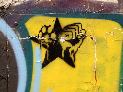 graffiti of a yellow star containing a fist and a dog paw