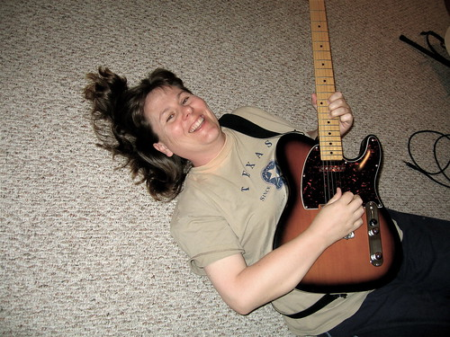 Maggie plays guitar on the floor