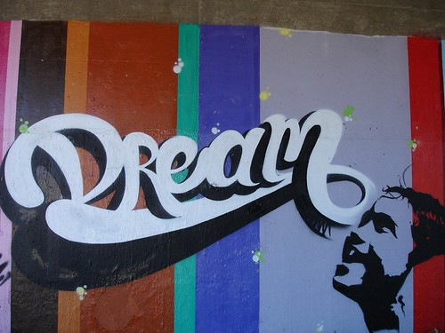 graffiti from Chico, CA: the word DREAM in script, with a child's delighted face looking up at it