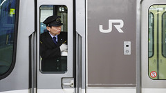 Subway driver in Osaka, unidentified Japanese train conductor observes passenger before giving a sign to move the train (Marco Crupi Visual Artist) Tags: train staff platform safety uniform profession worker work man security guard british carriage urban assist city controller crew travel underground windshield tram serious rigor vehicle permit skill standards doors trade visibility duties public passenger station technology subway transportation inspector looking transport employment person railway conductor cap job adult driver behavior