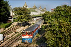DF2055 departs Yangon Central with the magnificent station as a backdrop. (Trains In Tasmania) Tags: myanmar yangon train passengertrain myanmarailways diesellocomotive trees ef35350mm13556lusm canoneos550d trainsintasmania stevebromley railwaystation station yard railwayyard locomotive