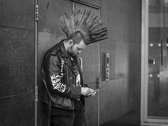 A Thorny Subject (Leanne Boulton) Tags: monochrome urban street candid portrait portraiture streetphotography candidstreetphotography candidportrait profile streetportrait streetlife man male face facial expression smoke smoker smoking cigarette style stylish fashion punk mohawk mohican mahican hairstyle hairspray leather spikes tone texture detail naturallight outdoor light shade city scene human life living humanity people society culture canon 5d 5dmkiii 70mm character ef2470mmf28liiusm black white blackwhite bw mono blackandwhite glasgow scotland uk