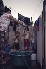 Taking a bath (Syahrel Azha Hashim) Tags: openair watershortage sony 2016 shallow holiday container mabulisland details portraiture a7ii bath house waterpipe sabah local humaninterest ilce7m2 shower dof poverty woodenhouse portrait syahrel sonya7 simple kid getaway handheld home colorimage vacation hardtime children wet unfortunate naturallight moment colorful nocleanwater 35mm travel simplelife prime outdoor colors light family malaysia bathing detail