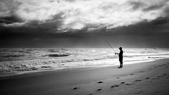Fishing - Melbourne, Florida - Black and white street photography (Giuseppe Milo (www.pixael.com)) Tags: photo fineart streetphotography sunstar sky xpro2 monochrome street unitedstates white city faceless black fuji2314 urban florida sea sun man contrast silhouette candid light blackandwhite photography fuji bw fisherman usa geotagged figure indialantic us onsale