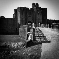 Defying Guidelines (alistairwilliamson03) Tags: street old city bridge bw white lake man black castle grass stone wales fence town view streetphotography cobbled cobble welsh moat cobbles caerphilly