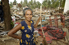 A woman sweeps up the remains of her home