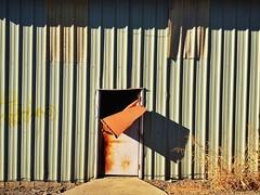 Bent (misterbigidea) Tags: explore rust patina warehouse crusty rusty door shadow lines orange mystery facesinplaces iseefaces urban doorway metal tongue