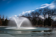 Icing (Anthony P26) Tags: category eskisehir kanlikavakpark landscape places travel turkey longexposure water clouds cloudblur sky bluesky trees park citypark pond ice snow fountain canon1585mm canon70d canon travelphotography landscapephotography buildings spray outdoor