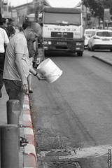 Throwing bad things (barak.shacked) Tags: road street blackandwhite man bucket jerusalem streetphotography ירושלים