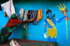 Shiva. New Delhi, India (Marji Lang Photography) Tags: street travel people woman india colors wall composition painting photography colorful image couleurs delhi indian streetphotography documentary clothes laundry dailylife shiva hindu wallpainting slum newdelhi drying slums motibagh travelphotography hindugod canon5dmii marjilang