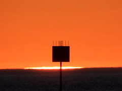 Fire on the Water (mikecogh) Tags: glenelg sunset channelmarker horizon orange glow sun blob deterrent spikes silhouette